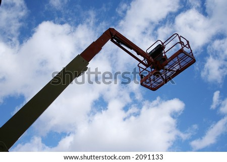 cherry picker against blue sky with scattered clouds