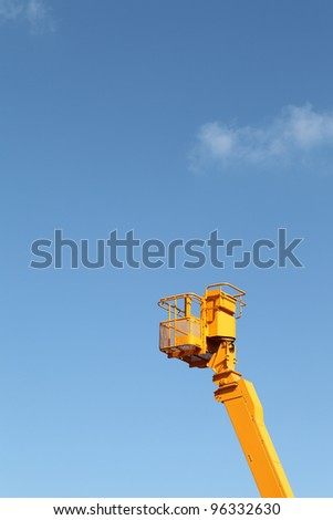 Cherry picker platform against a blue sky