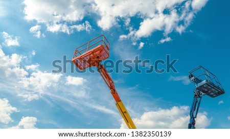 Cherry pickers on blue sky background. Boom with lift buckets of heavy machinery. Panorama of the platforms of the telescopic construction lifts in summer.