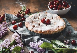 Cherry pie decorated with cherries on a table with sprigs of lilac