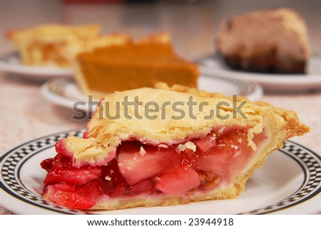 cherry pie in focus with other slices of pie out of focus on a diner table