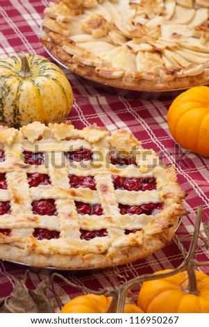 Cherry pie with lattice top, and apple pie on fall themed napkin, and mini pumpkins.