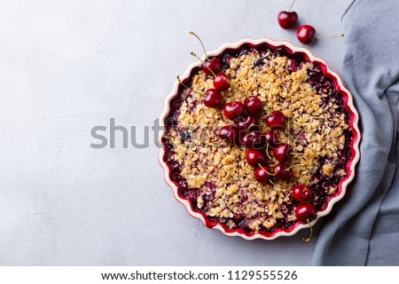 Cherry, red berry crumble in baking dish. Grey stone background. Top view. Copy space.