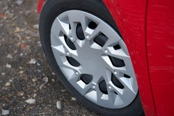 Cherry red car front detail with big light-alloy wheel.