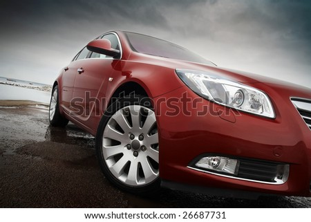 Cherry red car front detail with big light-alloy wheel - stock photo