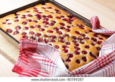 Cherry sponge cake after baking in tin with towel