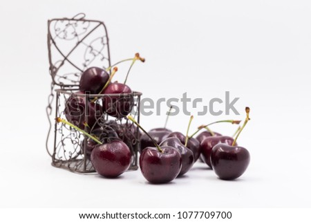 Cherry spread on white blackground,some put in wire basket and some put in plastic cartoon heart. tell love someone in valentine day or take care your health. #1077709700