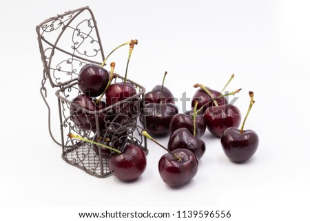 Cherry spread on white blackground,some put in wire basket and some put in plastic cartoon heart. tell love someone in valentine day or take care your health. #1139596556