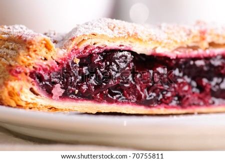 Cherry strudel with white dishes close up