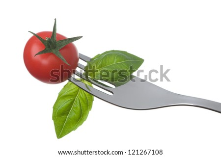 cherry tomato and basil leaves on a fork against a white background