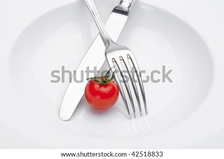 cherry tomato on a plate with fork and knife isolated on white