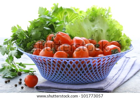 Cherry tomatoes and herbs in a wicker basket