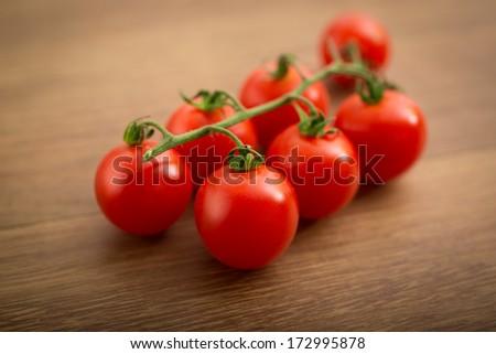 Cherry Tomatoes - Fresh organic cherry tomatoes on a wooden table. Studio shot.