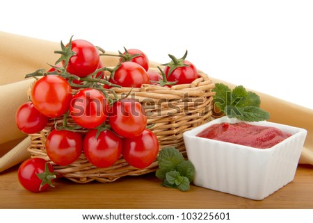 Cherry tomatoes in a basket and tomato paste