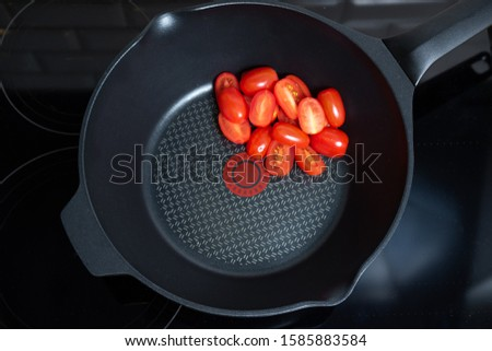 cherry tomatoes in a pan. selective focus. Stages of cooking vegetarian pasta. Vegetarianism concept