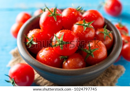 Cherry tomatoes in ceramic bowl on blue rustic wooden background. Selective focus. #1024797745