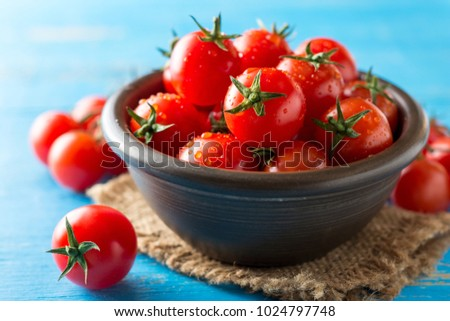 Cherry tomatoes in ceramic bowl on blue rustic wooden background. Selective focus. #1024797748