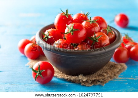 Cherry tomatoes in ceramic bowl on blue rustic wooden background. Selective focus. #1024797751