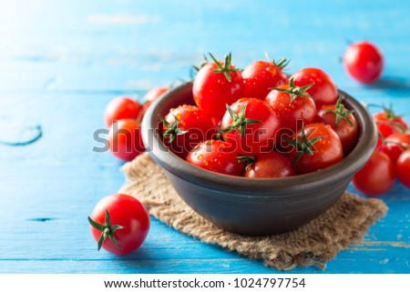 Cherry tomatoes in ceramic bowl on blue rustic wooden background. Selective focus. #1024797754