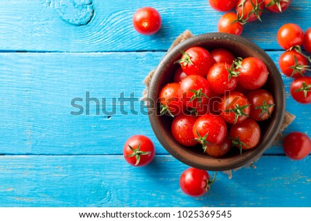 Cherry tomatoes in ceramic bowl on blue rustic wooden background. Top view. Copy space. #1025369545