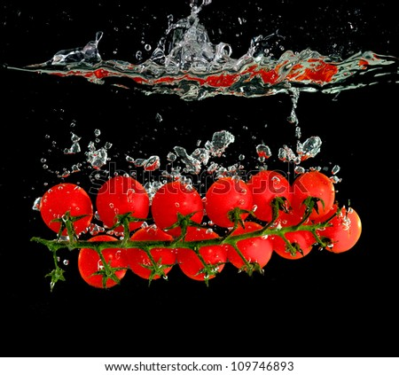 cherry tomatoes in the water on black background