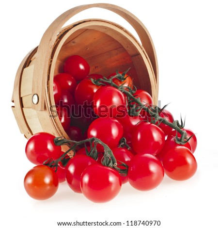 cherry tomatoes in wooden basket isolated on white background
