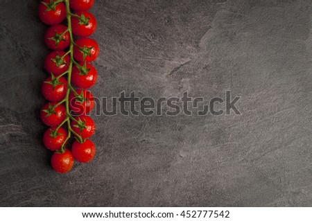 Cherry tomatoes lying on a black stone table, modern concept. #452777542