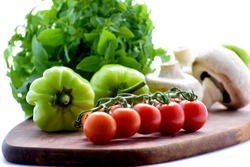 Cherry tomatoes on a branch, green pepper, champignons and basil on a wooden board