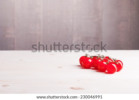 cherry tomatoes on a light wooden table side view