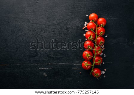 Cherry tomatoes on a twig on a wooden background. Top view. #775257145