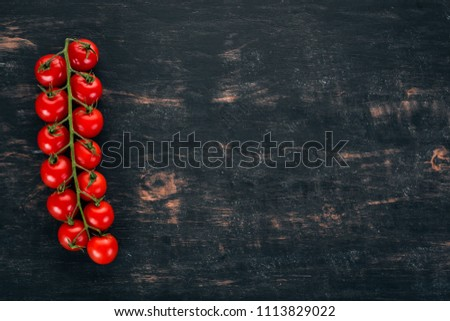 Cherry tomatoes on a twig. On a wooden background. Top view. Copy space. #1113829022