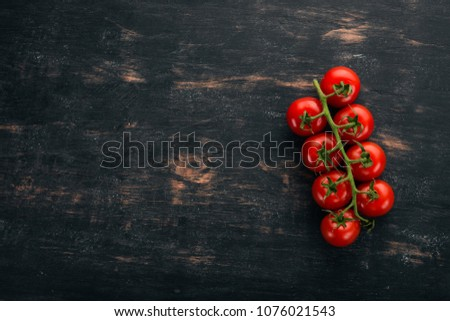 Cherry tomatoes on a twig. Top view. On a black wooden background. Copy space. #1076021543