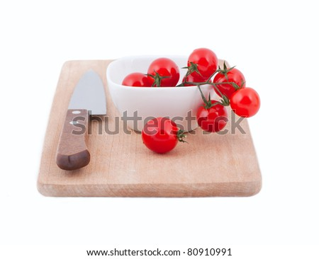 cherry tomatoes on a wooden board with a knife on a white background