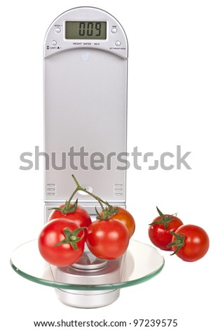Cherry tomatoes on electronic kitchen scales isolated over white background
