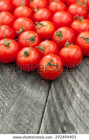 Cherry tomatoes on old wooden table. Vegetables background. Rustic style.
