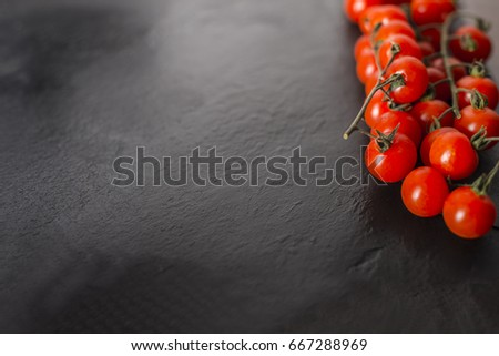 Cherry tomatoes over a black stone plate with copy space. #667288969