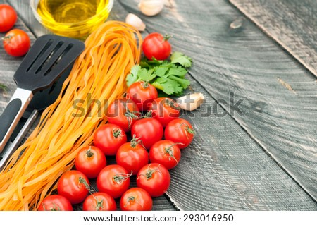 Cherry tomatoes, pasta, olive oil, garlic, herbs and pasta tongs on the old wooden background. Rustic style. Italian food. Selective focus