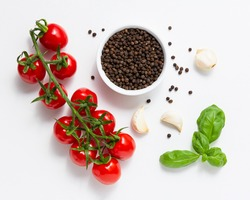 Cherry tomatoes with basil, allspice pepper and garlic on white background. Top view of fresh vegetables.