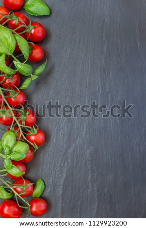 Cherry tomatoes with basil leaves on a dark slate background, vertical, top view, copy space #1129923200