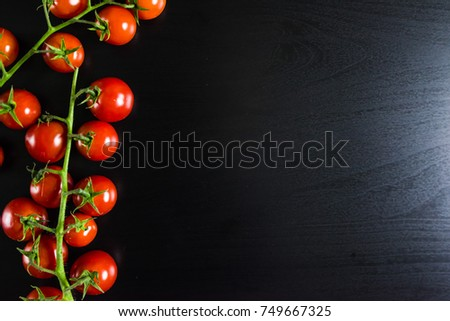 Cherry tomatos on black background. top view. #749667325