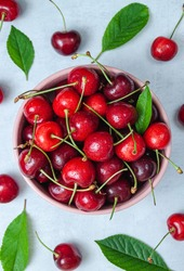 Cherry with leaf on plate and water drops on grey stone table. Ripe ripe cherries. Sweet red cherries. Top view. Rustic style. Fruit Background