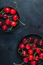 Cherry with leaf on plate and water dropsand on black stone table. Ripe ripe cherries. Sweet red cherries. Top view. Rustic style. Fruit Background