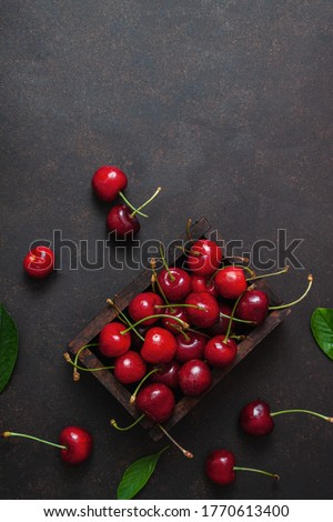 Cherry with leaf water drops on wooden box on dark brown stone table. Ripe ripe cherries. Sweet red cherries. Top view. Rustic style. Fruit Background