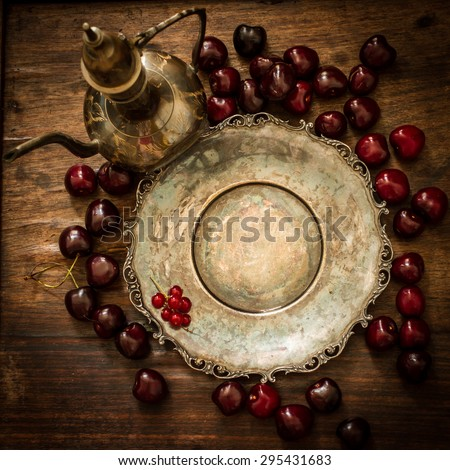 cherry with red currants and blueberries in a jug and a metal plate in oriental style on a background of wood #295431683