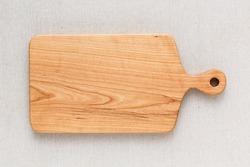Cherry wood cutting board on linen, handmade wood cutting board