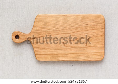 Cherry wood cutting board on linen, handmade wood cutting board