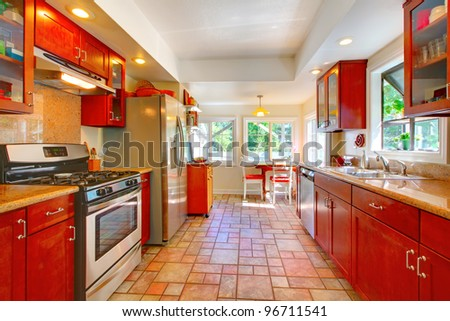 Cherry wood kitchen with tile floor and sunny table home interior.