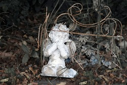 Cherub monument in a small cemetery appears to be forgotten, sitting in leaves and forest debris just beyond the edge of the lawn