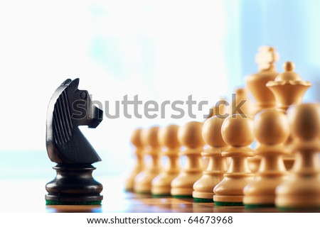 Chess black knight challenges white pawns abstract background