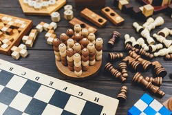 Chess board and chess figures, wooden cubes, puzzle games on dark wooden table. Popular logic  games for logical thinking.